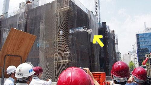 ドローン(矢印部分)を使って建築現場を空撮する様子