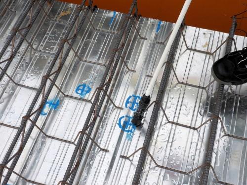 鋼床デッキプレート上で印を付けているところ。青い十字印は、従来の方法で墨出しした位置だが、誤差はほとんどない