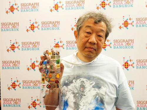 何十個ものバッジを手にした首都大学東京の今間俊博教授