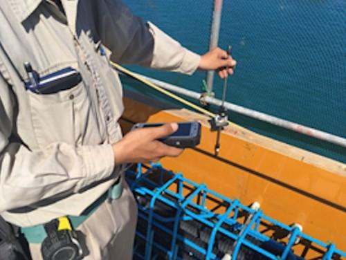 測量係はプリズムを持って測りたい場所に移動し、スマホで測量機から座標データを受信する