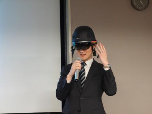 セミナーで講演するインフォマティクスの金野幸治さん。ダースベーダーを思わせるスタイルで壇上に登場した