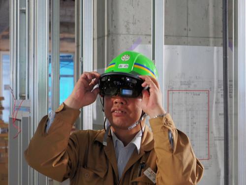 工事用ヘルメットをかぶってHoloLensを使うときは、ずり下がるのを手で押さえる必要があった(写真:特記以外は家入龍太)