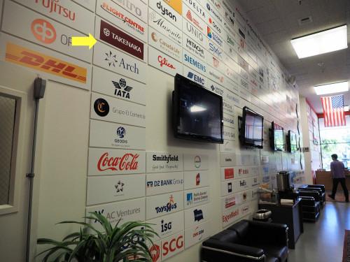 プラグ・アンド・プレイのオフィス内には、おびただしい数のスポンサー企業のプレートが上から参加した順に張ってある。竹中工務店のプレートはかなり上の方にあった