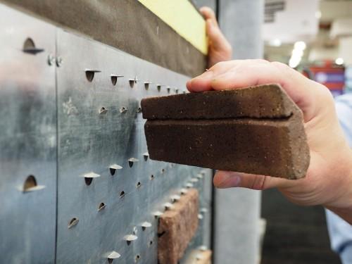 壁に爪つきの鉄板を張り、レンガ状のタイルの溝を引っかけて落ちないようにする