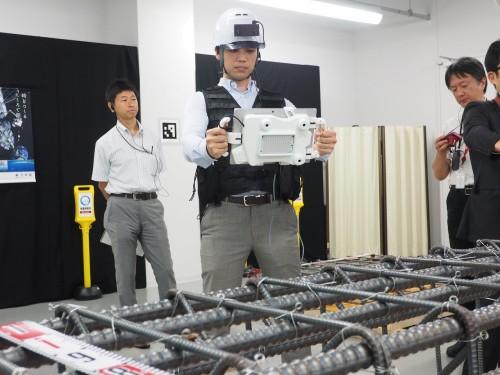 タブレットパソコンと3眼ステレオカメラが合体したスキャン装置を鉄筋に向ける