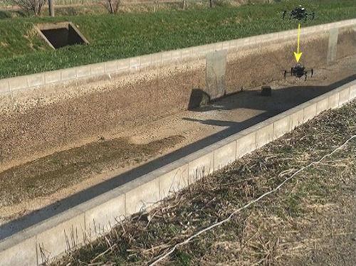 離陸したドローンが開水路内に降下し、低空飛行するイメージ(以下の写真、資料:特記以外はトップライズ)