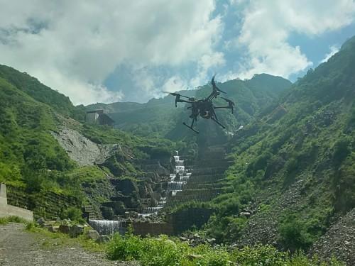 砂防施設の上空を飛行するドローン。通常のカメラと赤外線カメラの両方を備え、同時撮影が行える