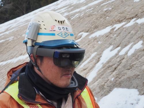 """HoloLensを着用した職人さんの目には、側溝を設置する際の基準線となる""""仮想水糸""""が見えている(写真:家入龍太)"""