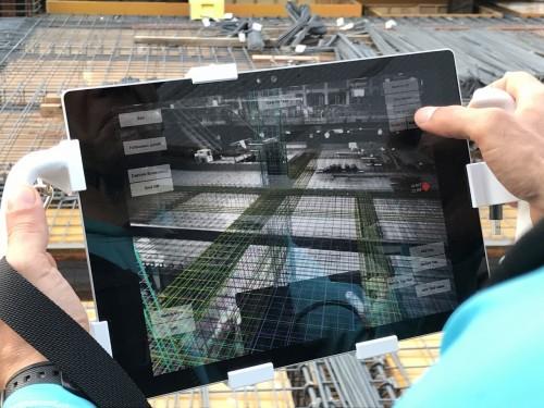 タブレットパソコンと3眼ステレオカメラが合体したスキャン装置を鉄筋に向ける技術者(写真:大林組)