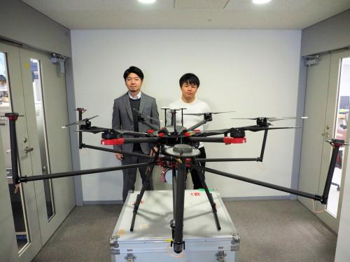 テラドローンが発売するドローンレーザー測量システム「Terra Lidar」を搭載したドローン。後方に立つのは同社日本統括責任者の関隆史氏(左)と事業戦略部UTM事業部の中新健太氏(右)(写真:家入龍太)