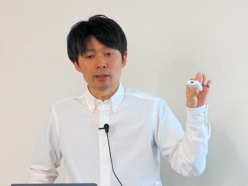 IoT機器を手に講演するエコモット経営企画部マーケティンググループマネージャーの國塚篤郎氏(写真:家入龍太)