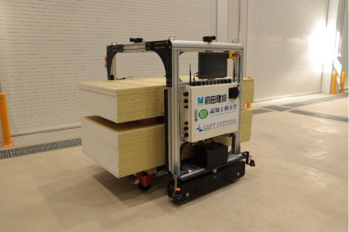 平台車に積んだ資材を自動搬送するAGV。上部にカメラらしきものが搭載されているようだ(写真:前田建設工業)