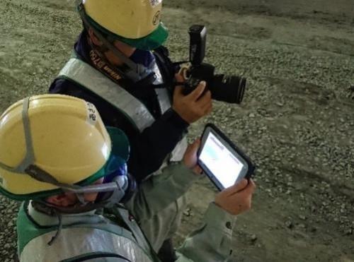 奥のデジカメでトンネル坑内を撮影すると、そのデータが無線LANで手前のタブレットパソコンに自動転送される