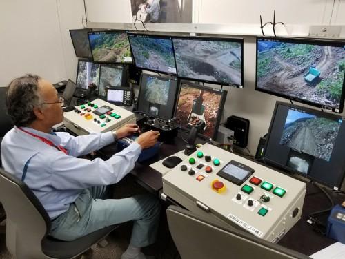 操作室から作業を行うオペレーター。不整地運搬車は自動的に走行するので、バックホーによる整地や積み込み作業に専念できる