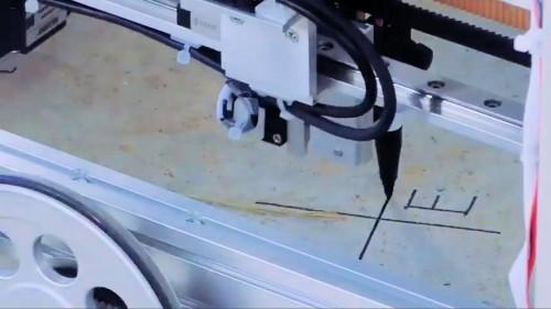 搭載されたペンプロッターで床に墨出しを行っているところ