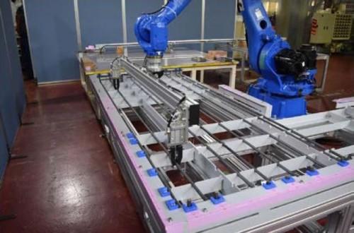鉄筋自動組み立てシステム「Robotaras」の試作機。ロボットアームの先端部に鉄筋保持治具を取り付け、鉄筋を型枠内に配置しているところ