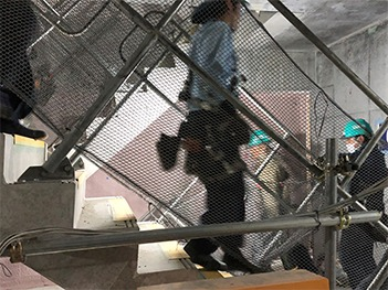 場内スピーカーで指示された避難経路を通って避難する作業員
