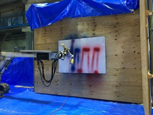オペレーターが操作して描いた赤線の上を、自動吹き付けシステムが青線でなぞる上書き再現試験