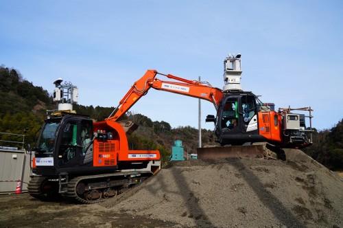 5Gによる遠隔操作で掘削した土を積み込む油圧ショベル(右)とクローラキャリア(左)