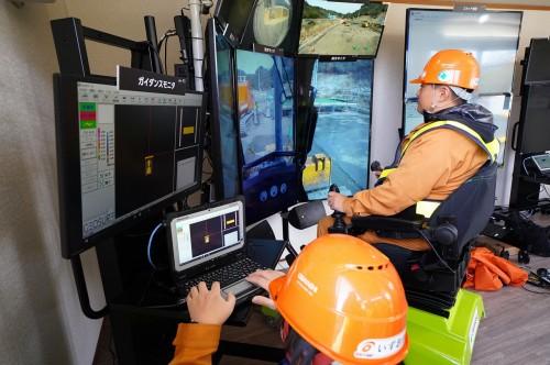 5Gでリアルタイムに建機を遠隔操作するオペレーター(以下の写真、資料:KDDI、大林組、NEC)