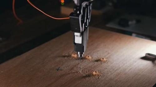 指示された墨出し位置に自動的に穴をあけるロボット