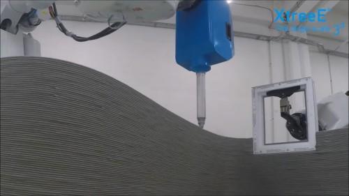 2台のロボットを使い、窓枠の周囲に壁を自動造形する3Dプリンター