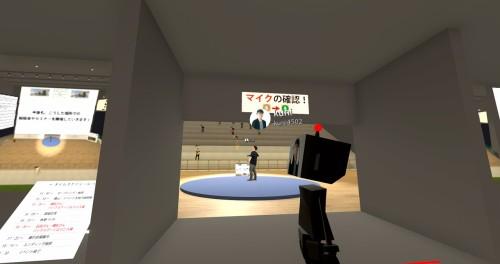 主催者あいさつが行われているステージをバックヤードから見たところ。手前は出番を待つ横松氏。ステージへの通路には、マイクのスイッチをオンにするようにという注意書きが掲示されています
