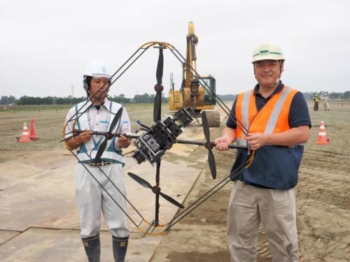 日ごろ、地上で使っている工一郎を、今日はドローンに載せて空撮にチャレンジする。右はパイロットを務める岩崎 企画調査部精密農業チームの河手健一さん