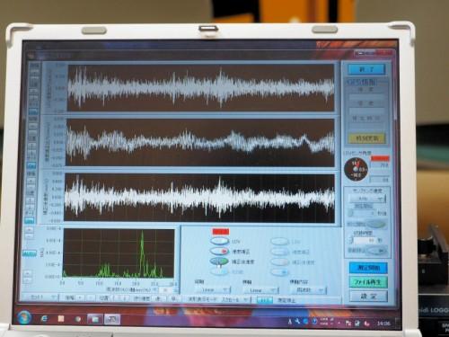 データ収録部のパソコン画面。上から対象物の振動波形、本体の振動波形、対象物の振動を本体の振動で補正した3つの波形が表示されている。左下の緑色のグラフは振動の周期スペクトルをリアルタイム表示したもの