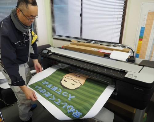A0プラス対応大判複合機「HP DesignJet T830 MFP」で、現場のオリジナルポスターを印刷する新日本工業の監理技術者、鈴木努氏