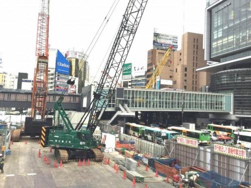 渋谷駅前に建つ渋谷ヒカリエ(右)と通りを隔てて向かい合う東棟の工事現場(左)