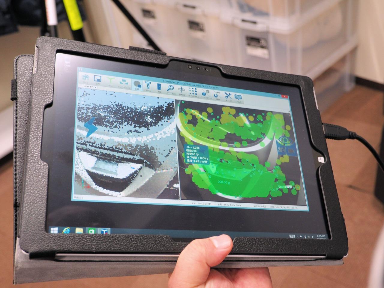 手にしたタブレットパソコンにリアルタイムに表示される点群データ(左)と計測済みの部分を表す緑色のマーク(右)