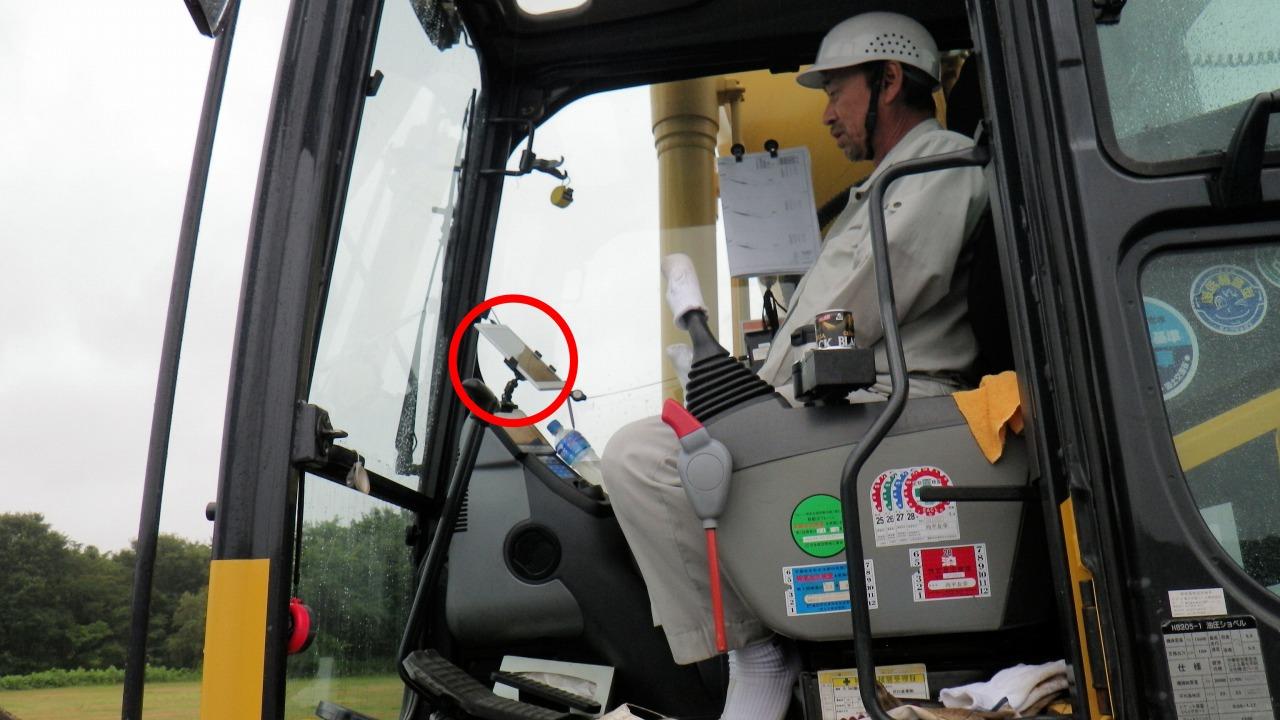 バックホーの運転席に設置されたタブレット端末(円内)