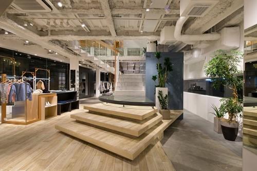 ステージ、ベンチ、商品陳列棚など店舗の機能を担う家具として設計した階段。天井はスケルトンとして設備がむき出しになっている