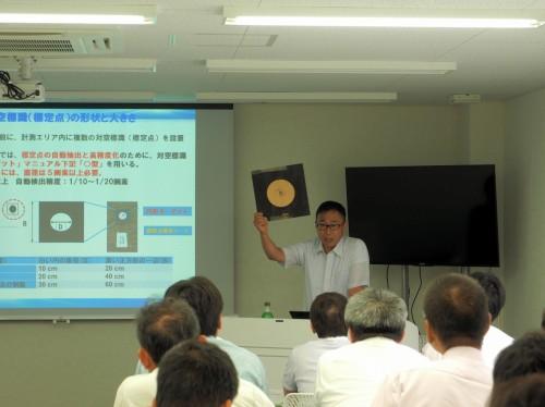 神戸トレーニングセンタで開催された「i-Construction UAV写真測量講習会」。ドローンによる空撮用の対空標識を掲げて説明する講師の大谷仁志さん