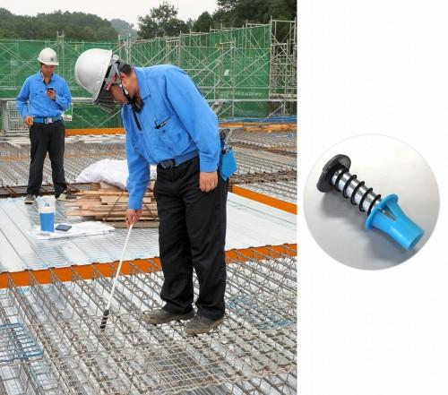 インサートの墨出し作業を想定して実証実験を行う田中所長。ヘルメットの下にはAR用ゴーグル「HoloLens」を装着している(左)。吊りボルトを固定するために床板に埋め込まれる「インサート」(右)