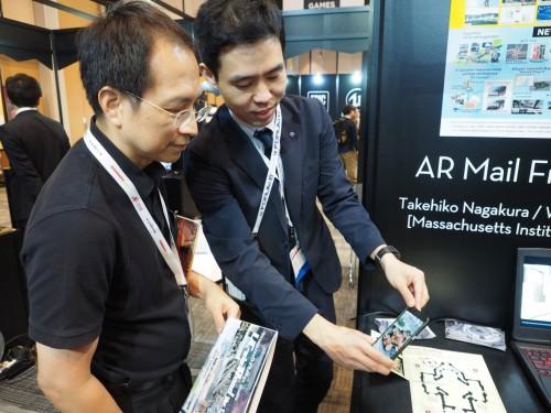 絵はがきにスマホをかざすと建物の3D映像が見られる「AR Mail From Harbin」を体験する来場者(左)と説明するフォーラムエイト社員(右)
