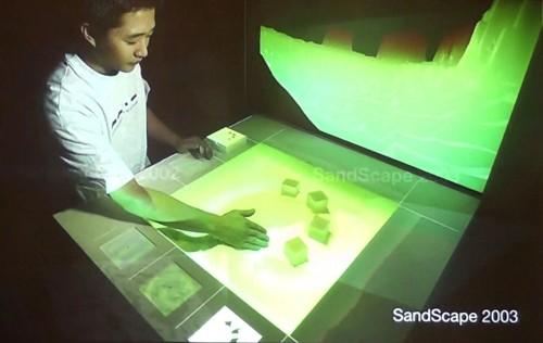 「SandScape 2003」。手で砂山の形を変えると、それに応じて等高線やヒートマップなどの映像がリアルタイムに投影される