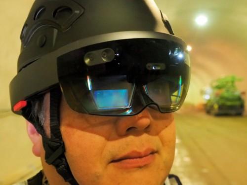 HoloLensを着用して現場を見る藤原氏。今回、HoloLensをピッタリ取り付けられるヘルメットも用意した