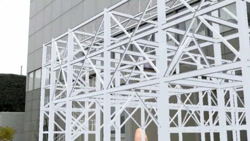 増築工事をイメージした使用例。HoloLensを着用して実物の建物を見る(上)。すると建物の前には鉄骨が実物大で立体的に見える(下)