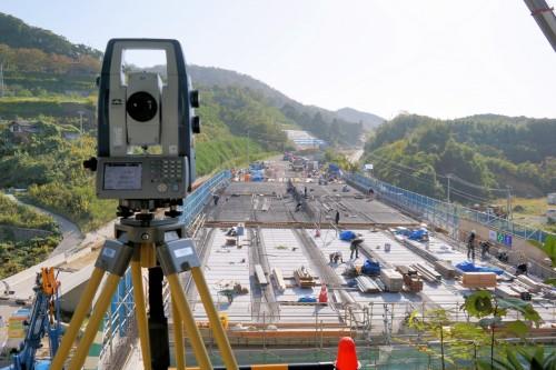 橋面全体を見渡せる丘の上に設置された自動追尾型トータルステーション。生コンの打設過程を自動的に測量し、記録していく