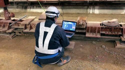 生コンクリート打設中、現場用パソコンでスマートセンサのデータを見守る施工管理技術者