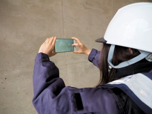 コンクリートの表面をスマートフォンで撮影する