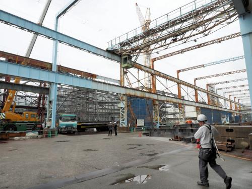 鉄骨工場のすぐ奥で新事務所ビルの工事が行われている。工場でできあがった鉄骨はクレーンで現場に直送できる